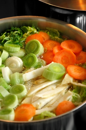 boiling: A boiling pot of vegetable soup on top of the stove.  Focus across the middle of image.