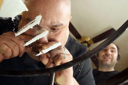 Una imagen sobre el uso indebido de drogas. Hombre inhalaci�n l�neas de coca�na sobre una sucia mesa de cristal mientras que otro espera su turno. Vista desde abajo ya trav�s del vidrio.  Foto de archivo - 2780717