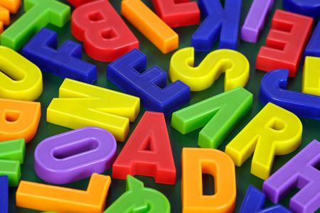 Background image of magnetic alphabet letters.  Focus is across the middle. Stock Photo - 2869186