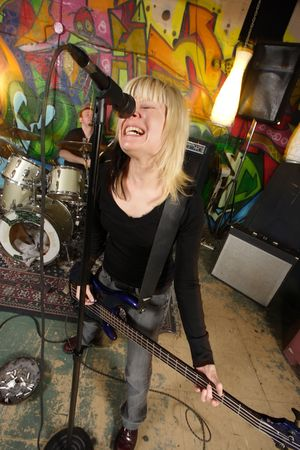 Female bass player screaming into a microphone.  Focus on singers face - drummer blurry in the background.  Shot with slow shutter speed and strobes - motion blur visible in some areas. Stock Photo - 2875065