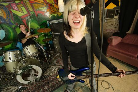 Female bass player screaming into a microphone.  Focus on singers face - drummer blurry in the background.  Shot with slow shutter speed and strobes - motion blur visible in some areas. Stock Photo - 2875067