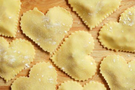 Heart-shaped homemade pasta sitting on a wooden countertop. Stock Photo