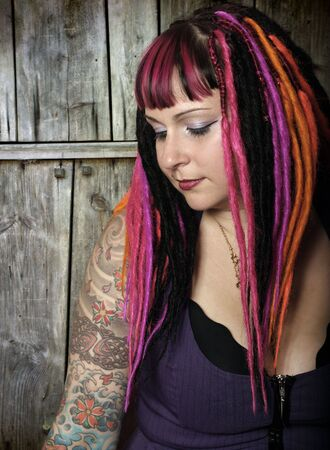 Portrait of a beautiful female goth with dreadlocks in front of an old wooden door.  Slightly desaturated. Stock Photo - 3104451