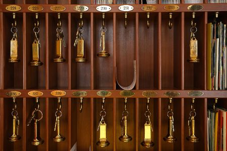 hotel stay: Vintage hotel front desk key rack. Focus on the top row of keys.