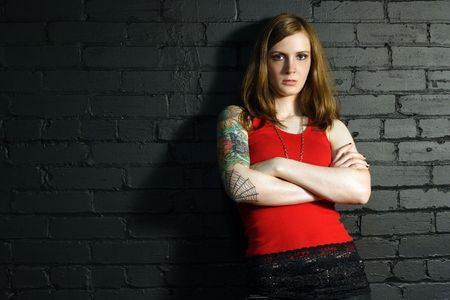 arm tattoo: A young female with full arm tattoo leaning up against a black brick wall. Stock Photo