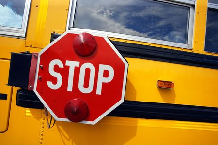 school bus: Side view of a school bus and its stop signal.