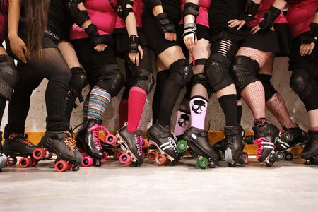 The roller skates and legs of a female Roller Derby team. Stock Photo