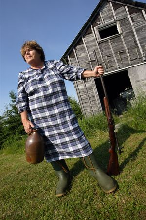 redneck: Moonshine Mary stands proud protecting her moonshine with a rather large shotgun. Stock Photo