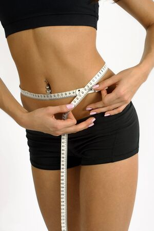 A tanned slim young woman measuring her waistline.  Stock Photo