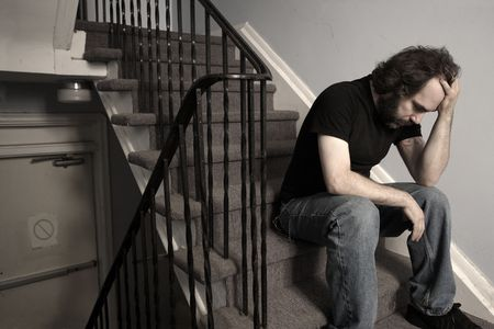 stairwell: A male adult with overwhelming depression sitting in the stairwell of his apartment building.  Desaturated.  Stock Photo