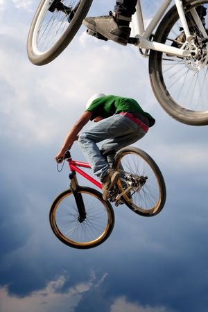airborne vehicle: Two BMX bikers high up in the air.  Some motion blur on both bikers.