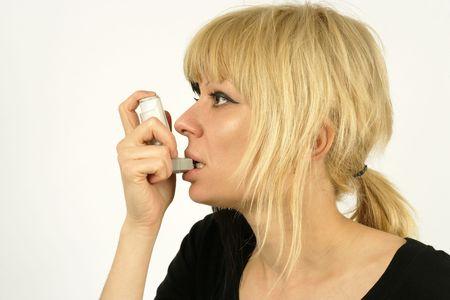sufferer: An asthma sufferer using an inhaler.  Stock Photo