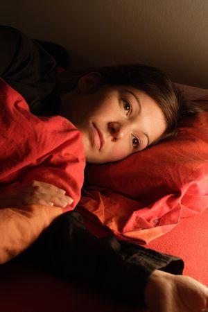 sleeplessness: Bella donna sdraiata a letto cercando di addormentarsi. Immagine di insonnia, insonnia, stress, tristezza, ecc illuminati da luce una notte accanto al letto. Archivio Fotografico