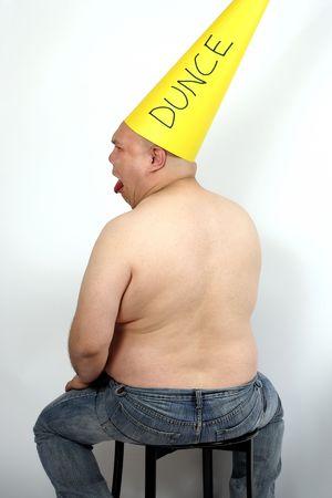 ingannare: Fool seduta in un angolo che indossa un berretto somaro. Archivio Fotografico