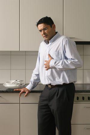angor: L'homme dans la fin de la trentaine debout dans sa cuisine d'une dose de br�lures d'estomac apr�s un repas. Banque d'images
