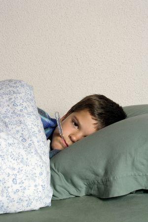 krankes kind: Krankes Kind mit Thermometer, frustriert auf seine Krankheit, Ruhe im Bett. Lizenzfreie Bilder