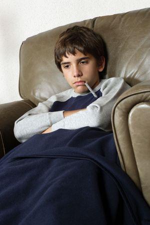 krankes kind: Krankes Kind sitzt in gro�en Leder-Sessel mit einem Thermometer in seinem Mund.