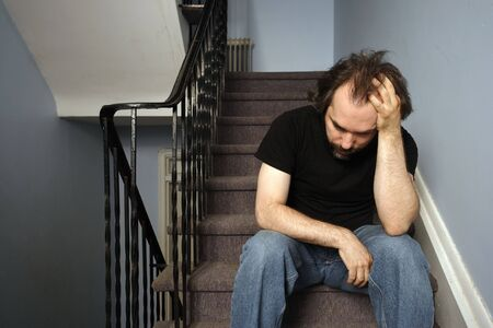 stairwell: A male adult with serious depression sitting in the stairwell of his apartment building.
