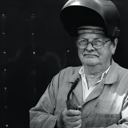 A senior in his 60's taking a break from his job as a welder. photo