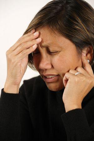 An attractive Asian female with a migraine, headache, or earache. photo