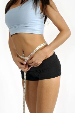 허리의 잘룩 한 선: A tanned slim young woman measuring her waistline.