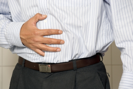 Closeup of a man having stomach pain or indigestion. Stock Photo