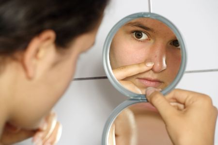 Young teenage female holding a mirror looking at her pimple with concern. photo