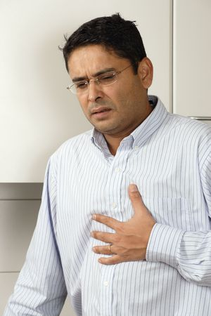 heartburn: Man in his late thirties standing in his kitchen having a dose of heartburn after a meal. Stock Photo