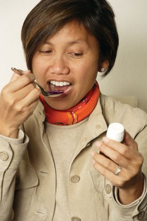cough medicine: An Asian female in her early 40s taking a spoonful of cough medicine.