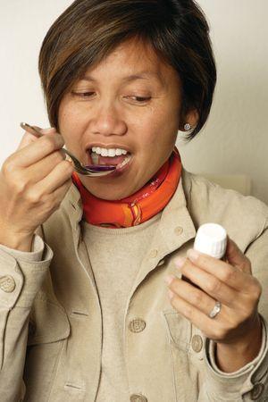 cuiller�e: Une des femmes d'Asie au d�but de ann�es 40 en prenant une cuiller�e de la toux m�decine. Banque d'images