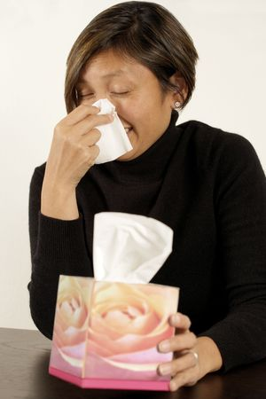 Asian woman sneezing or blowing her nose.  Design on tissue box is one of my flower images in my portfolio. photo
