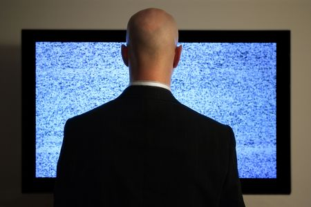 A man watching a blank or static screen of his television. photo