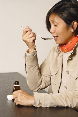 early 40s: An Asian female in her early 40s taking a spoonful of cough medicine.