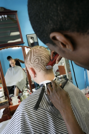 barbershop: A barber cutting a pattern into a blond mans short hair. Three model releases attached. Third model release is for the photo in the frame on the wall, which has been edited in from an image from my portfolio. Property is a barbershop and tattoo studio -