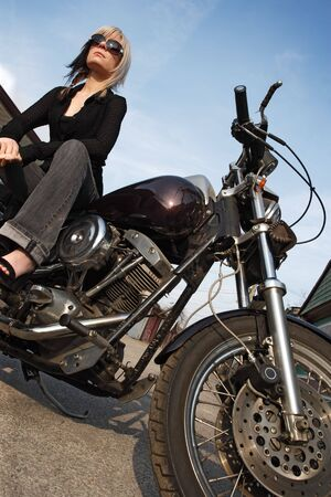 A beautiful blonde female sitting on a motorcycle. photo