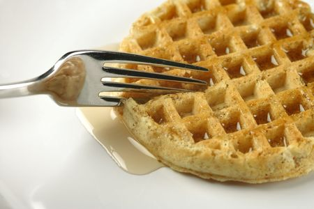 Closeup of a fork cutting through a waffle covered with maple syrup.