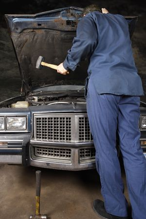 A bewildered mechanic about to use a hammer to take his frustrations out on the engine of an old car. Stock Photo - 4718251