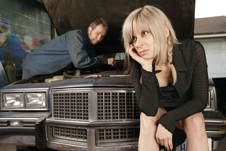 auto repair: A frustrated blond woman in her thirties waits for a mechanic to fix her old car. Stock Photo