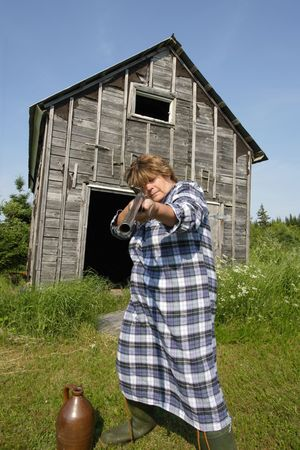 wants: Moonshine Momma wants you off her property, or shell fill you full of holes from her rather large shotgun. Stock Photo