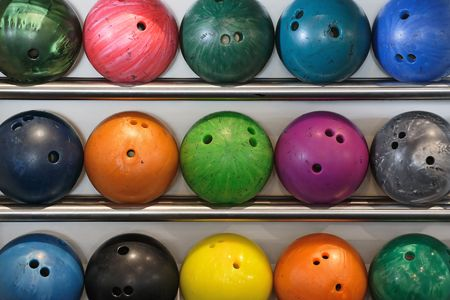 A rack of old worn bowling balls