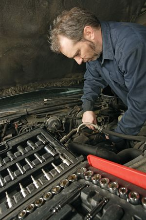A mechanic repairing an engine of an old car. Stock Photo - 4727558