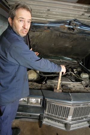 A bewildered mechanic unsure of what is wrong with the old car. Stock Photo - 4727556
