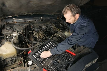 damaged: A mechanic repairing an engine of an old car. Stock Photo