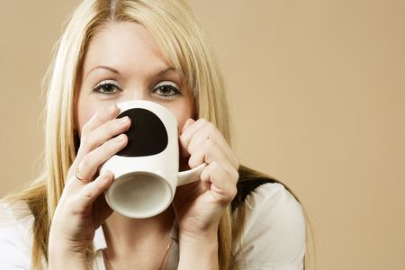 Happy female having a drink of coffee, hot chocolate, or tea. photo