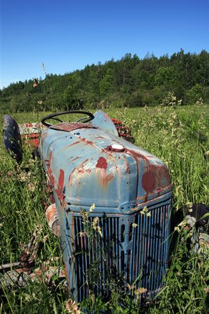An old abandoned tractor left to rot in a field. photo