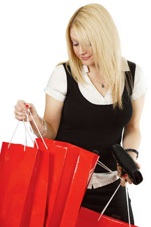 A beautiful young female looking in her shopping bags with a satisfied smile on her face. Stock Photo - 4862624