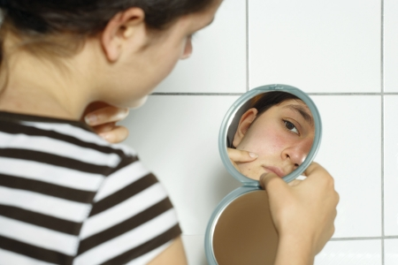 Young teenage female holding a mirror looking at her complexion with concern. photo