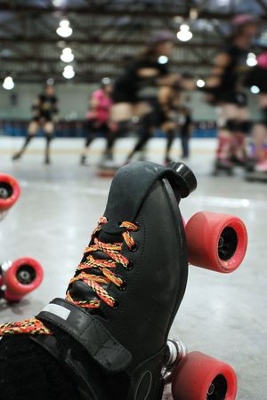 derby: An abstract image of the roller-skates of a fallen skater as her teammates in the background continue to skate around the track of the roller derby.