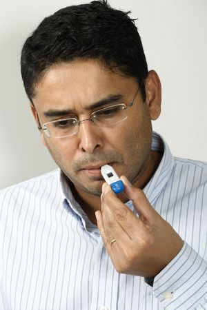 digital thermometer: A male in his 30s checking his temperature with a digital thermometer. Stock Photo