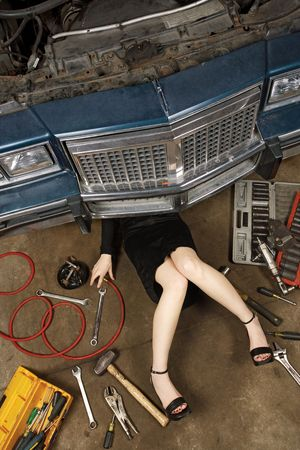 A female wearing a black skirt and heels doing repairs under the front of an old car from the early 80s. photo